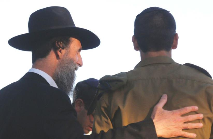 A haredi man embraces a youth from the Orthodox community who has joined the army (photo credit: MARC ISRAEL SELLEM)