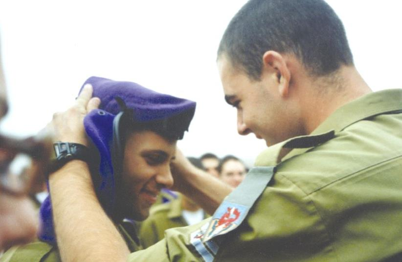 ST.-SGT. KOBI ICHELBOM, who was killed in action in the Gaza Strip, places a beret on one of his soldiers. (photo credit: AVIVA ICHELBOM)