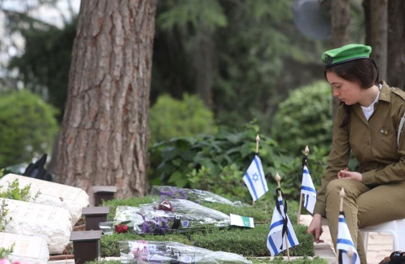 IDF soldier seats next to a gravestone at the national military cemetery on Mount Herzl in Jerusalem on Memorial Day, May 1, 2017 (photo credit: MARC ISRAEL SELLEM)