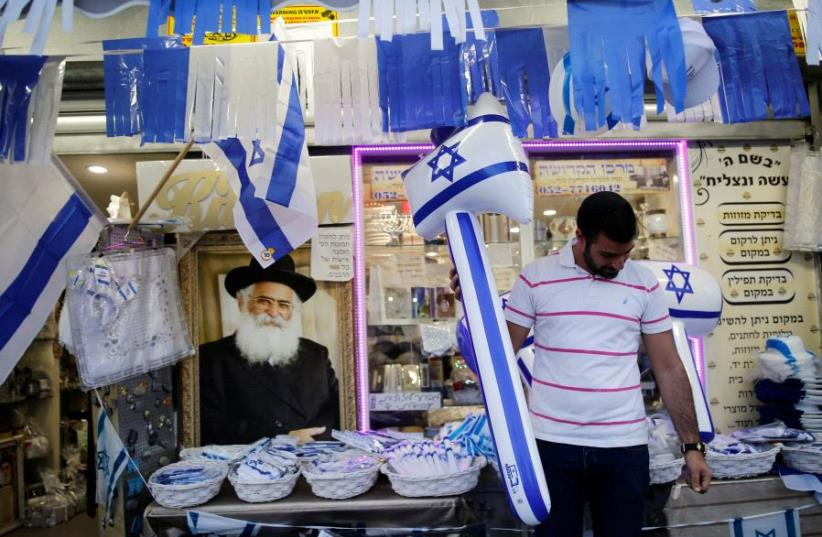 A man holds an inflatable hammer in front of a shop that sells items for Israel's upcoming Independence Day, held on May 12, in the southern city of Ashkelon May 8, 2016 (photo credit: REUTERS)