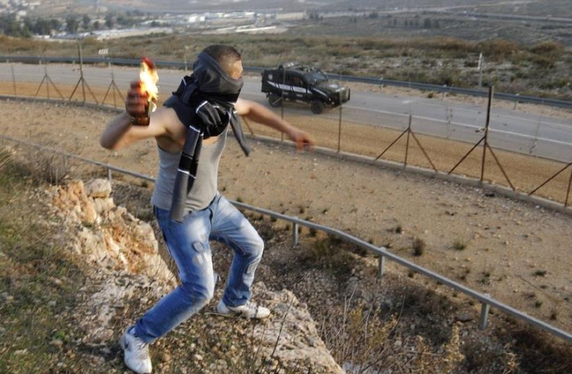 WHO IS paying him? A Palestinian throws a molotov cocktail at an Israeli jeep (photo credit: REUTERS)