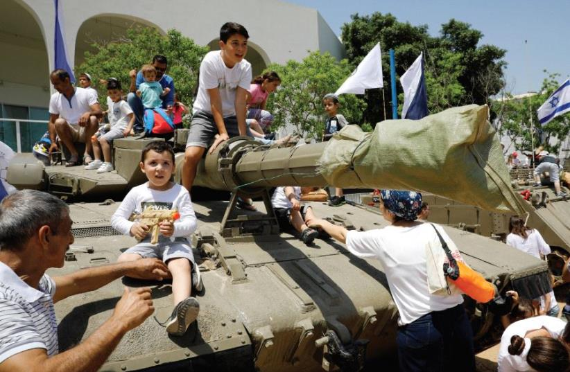 YOUNGSTERS PLAY on a tank as part of the celebrations for Israel's Independence Day marking the 69th anniversary (photo credit: REUTERS)