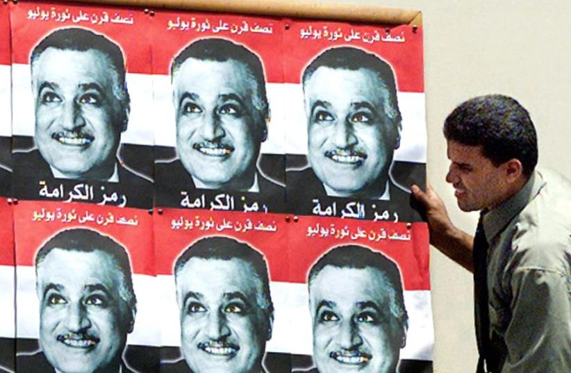 AN EGYPTIAN worker in 1967 mounts posters of president Gamal Abdel Nasser, whose action of closing the Straits of Tiran precipitated the Six Day War. (photo credit: REUTERS)