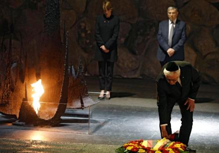 German President Frank-Walter Steinmeier touches a wreath during a ceremony commemorating the six mi