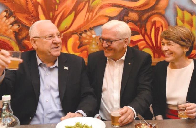 PRESIDENTS REUVEN Rivlin and Frank-Walter Steinmeier, together with Steinmeier's wife, Elke Budenbender, sample Israeli beer in the informal atmosphere of the Beer Bazaar at the Mahaneh Yehuda market. (photo credit: MARC NEYMAN/GPO)