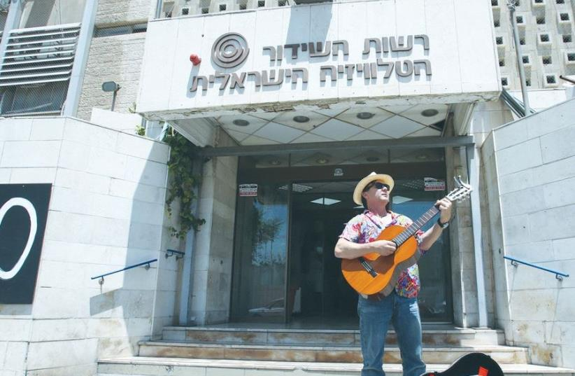 ARIEH O'SULLIVAN, 'IBA English News' anchor, plays the blues as the Israel Broadcasting Authority is shut down, in front of the IBA building in the capital's Romema neighborhood (photo credit: MARC ISRAEL SELLEM/THE JERUSALEM POST)
