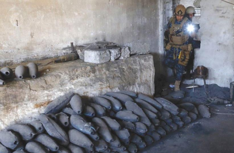 A MEMBER of the Iraqi Federal Police inspects yesterday a factory used by Islamic State to manufacture mortar shells in western Mosul. (photo credit: REUTERS)