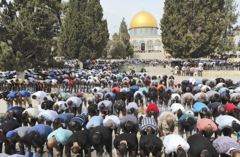 THE DOME of the Rock is seen in the background as Palestinian men take part in Friday prayers in Jerusalem. (photo credit: REUTERS)