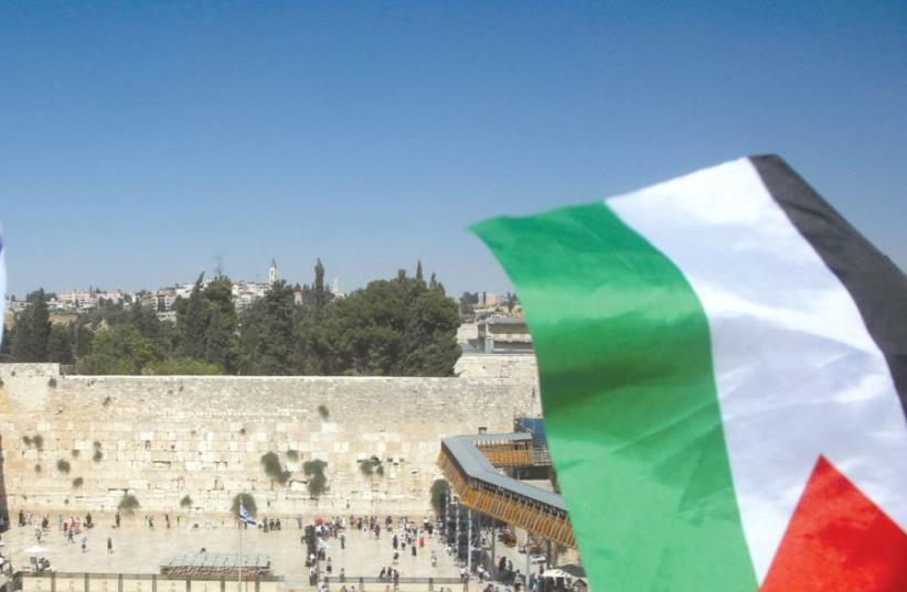 A Palestinian flag is seen waving in front of the Kotel (photo credit: REUTERS)