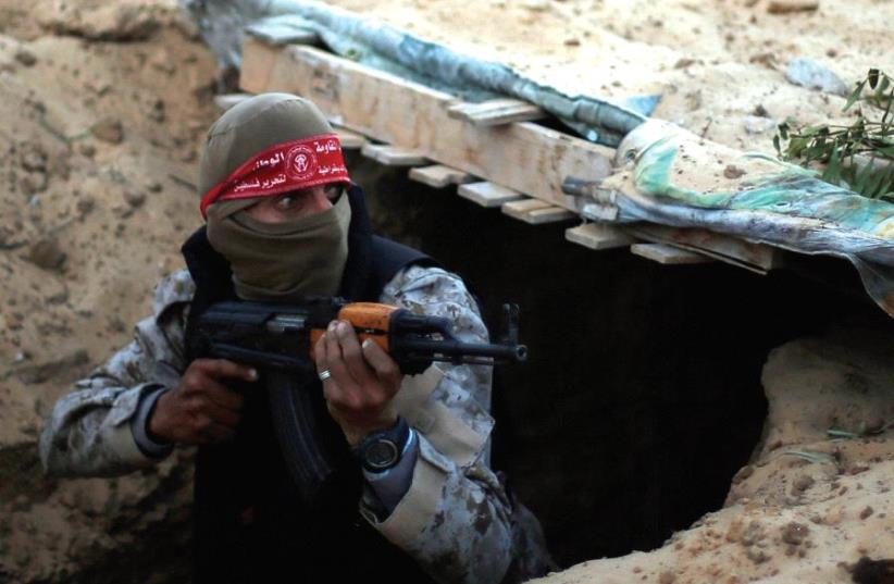 A Palestinian fighter takes part in a tunnel attack simulation during a graduation ceremony in Rafah, in the southern Gaza Strip, last November (photo credit: REUTERS)