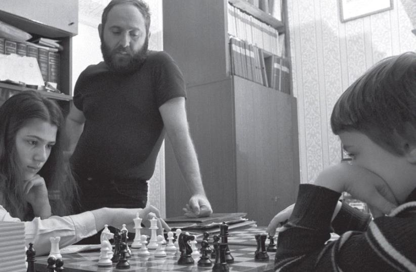 Laszló Polgár watches as his daughters Zsuzsa (left) and Zsófia play chess at the family's Budapest home in the early 1980s (photo credit: MTVA)