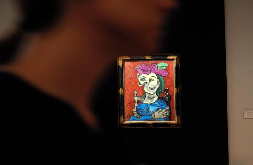 """Visitors walk around Pablo Picasso's depiction of Dora Maar in """"Femme assise, robe bleu"""", May 2017. (photo credit: JEWEL SAMAD / AFP)"""