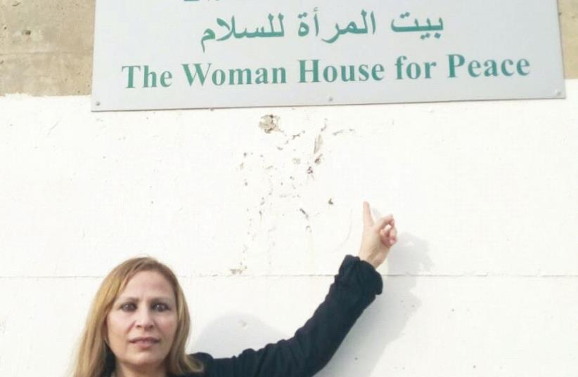 Dr. Janan Faraj Falah stands beneath the sign of the organization she founded in Acre to promote conflict resolution (photo credit: Courtesy)