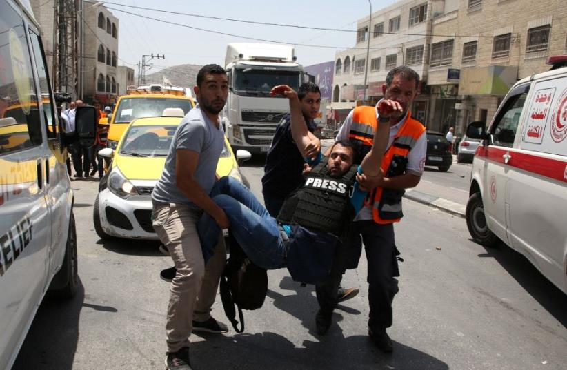 A wounded Palestinian reporter is carried by a medic and civilians on May 18, 2017 near the Hawara military checkpoint. (photo credit: JAAFAR ASHTIYEH / AFP)