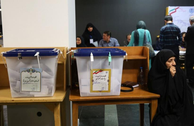 Electoral employees sits next to ballot boxes before closing vote for the presidential election in a polling station in Tehran, Iran, May 19, 2017. (photo credit: REUTERS)