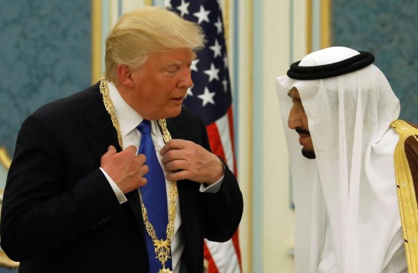 Saudi Arabia's King Salman bin Abdulaziz Al Saud (R) presents US President Donald Trump with the Collar of Abdulaziz Al Saud Medal at the Royal Court in Riyadh, Saudi Arabia (photo credit: JONATHAN ERNST / REUTERS)