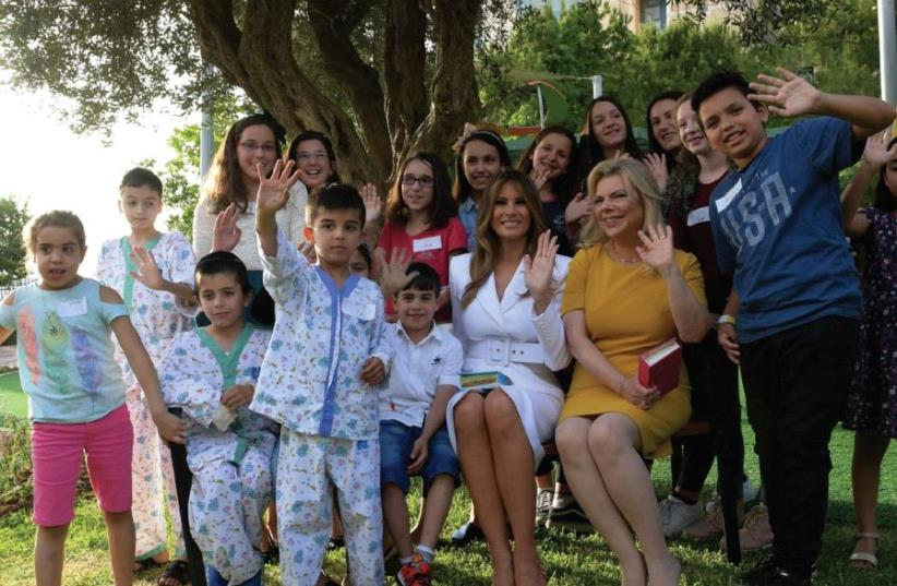 FIRST LADY Melania Trump and Sara Netanyahu, the wife of the prime minister, sit with children who are receiving treatment at Hadassah University Medical Center in Jerusalem's Ein Kerem yesterday. (photo credit: AVI OHAYON - GPO)