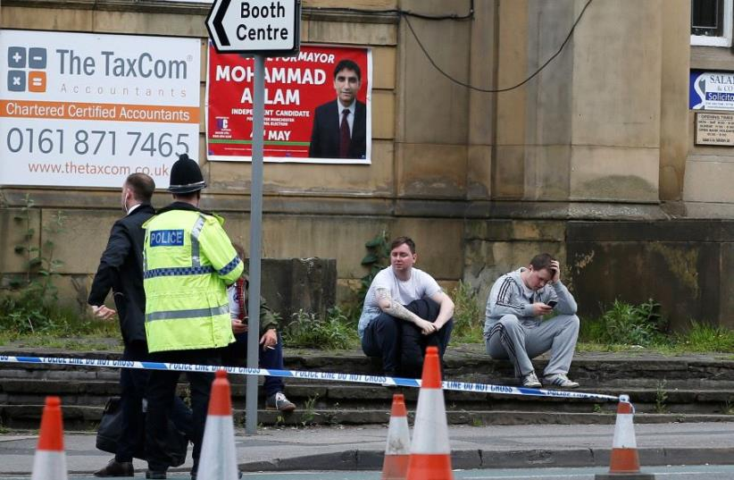 People sit next to a police cordon near to the Manchester Arena, Britain May 23, 2017 (photo credit: REUTERS)