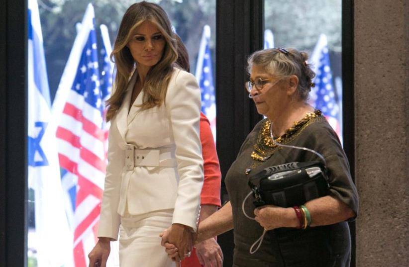 US first lady Melania Trump (L) holds the hand of Nechama Reuven, wife of Israeli president Reuven Rivlin, as they walk near American flags at Rivlin's residence in Jerusalem May 22, 2017 (photo credit: REUTERS)