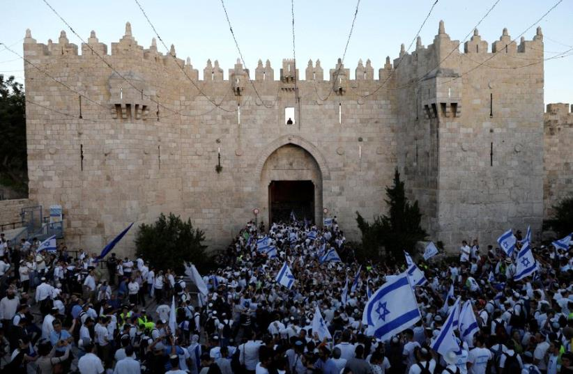 Israelis celebrate as they hold Israeli flags during a parade marking Jerusalem Day, the day in the Jewish calendar when Israel captured East Jerusalem and the Old City from Jordan during the 1967 Middle East War, just outside Damascus Gate outside Jerusalem's Old City May 24, 2017. (photo credit: RONEN ZVULUN/REUTERS)