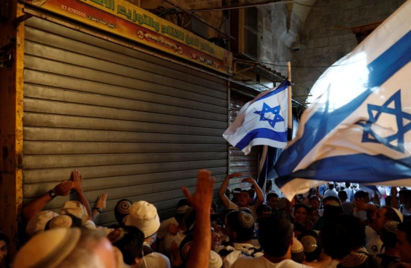 Israelis celebrate as they hold Israeli flags during a parade marking Jerusalem Day, the day in the Jewish calendar when Israel captured East Jerusalem and the Old City from Jordan during the 1967 Middle East War, at Damascus Gate in Jerusalem's Old City May 24, 2017.  (photo credit: RONEN ZVULUN/REUTERS)