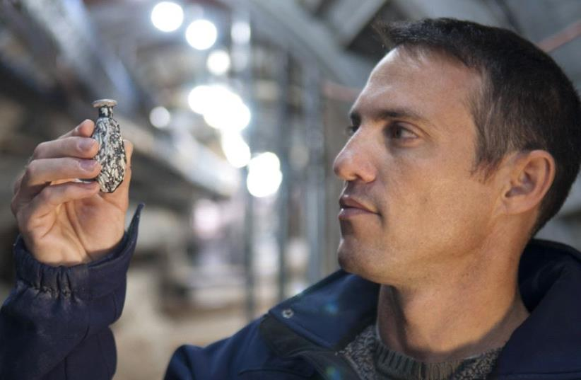 Nahshon Szanton holds a date-shaped glass juglet that was uncovered in the excavations of the street (photo credit: SHAI HALEVY/IAA)