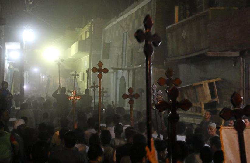 Mourners carry crosses and march after the funeral of Coptic Christians who were killed on Friday in Minya, Egypt, May 26, 2017.  (photo credit: MOHAMED ABD EL GHANY/REUTERS)