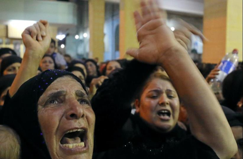 Relatives of victims of an attack that killed at least 28 Coptic Christians on Friday react at the funeral in Minya, Egypt May 26, 2017. (photo credit: REUTERS/MOHAMED ABD EL GHANY)