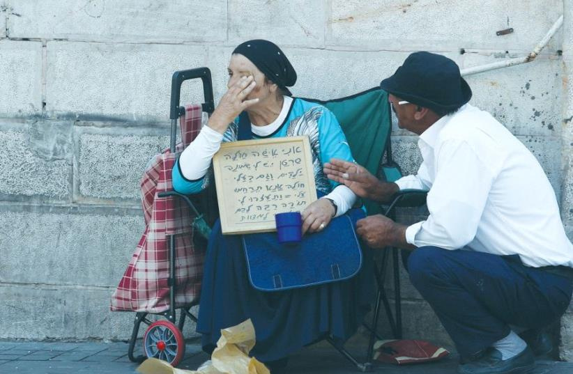 A PASSERBY stops to console a poor woman in Jerusalem in 2015. (photo credit: MARC ISRAEL SELLEM)