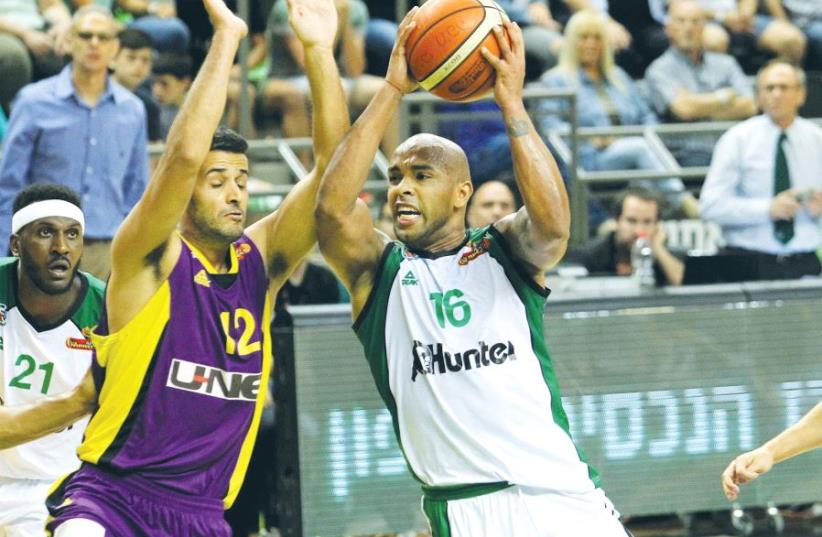 Maccabi Haifa forward Gregory Vargas (center) had 12 points and eight assists in last night's 101-70 win over Hapoel Holon and Shlomi Harush (left) in Game 2 of their quarterfinal series (photo credit: ERAN LUF)