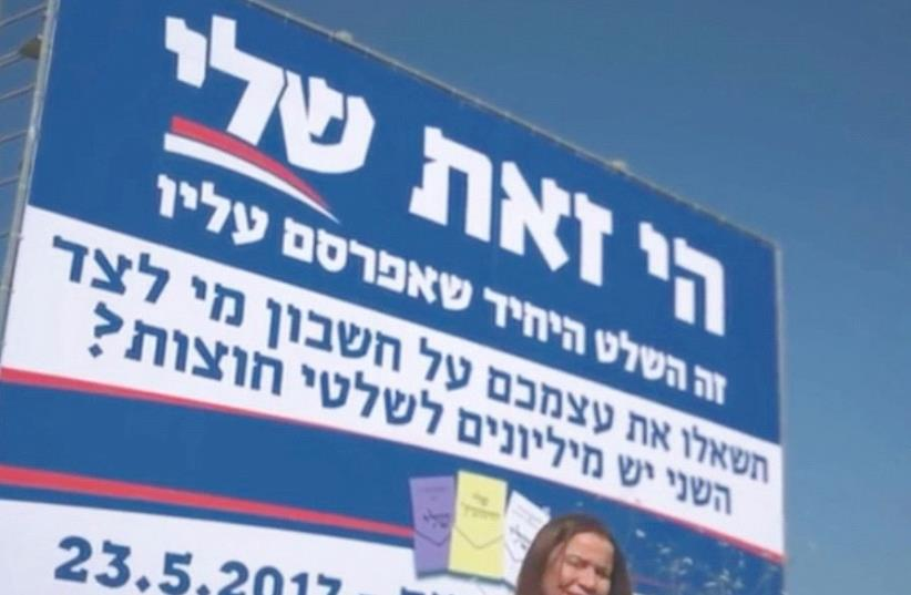 SHELLY YACIMOVICH poses in front of one of her campaign signs earlier this month. (photo credit: YOU TUBE)