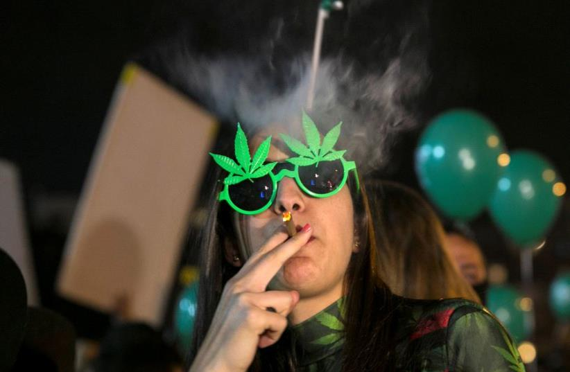 A woman smokes during an event marking Israel's government's approval of a new policy to decriminalize personal marijuana use in Tel Aviv, Israel February 4, 2017 (photo credit: REUTERS/BAZ RATNER)