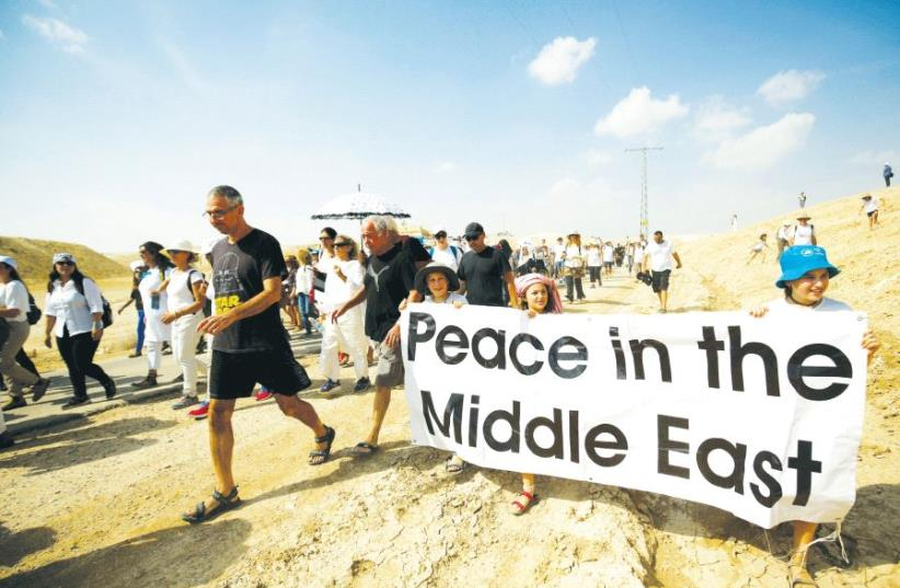 Demonstrators including Israeli and Palestinian activists take part in a demonstration in support of peace near Jericho last year (photo credit: REUTERS)