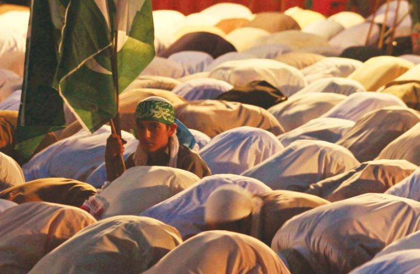 A SUPPORTER of Jamaat-e-Islami, a Pakistani religion-based political party, holds the national flag while sitting among others offering evening prayers in Islamabad, Pakistan. (photo credit: REUTERS)