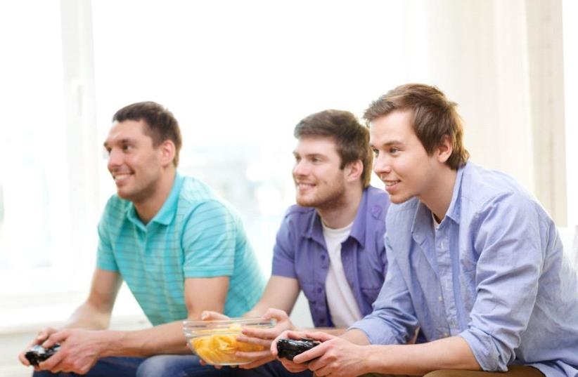 Young Americans playing video games (illlustrative) (photo credit: INGIMAGE)