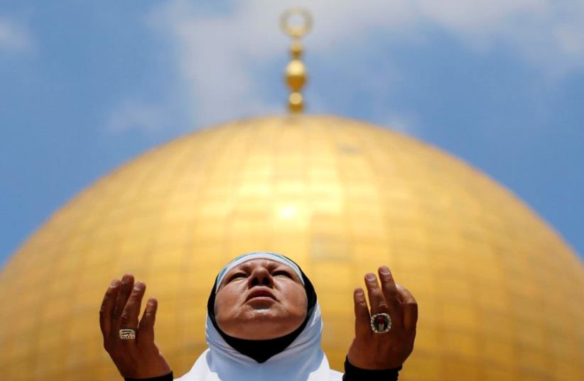 A Palestinian woman prays on the first Friday of the holy fasting month of Ramadan, at the Temple Mount in Jerusalem's Old City June 2, 2017. (photo credit: REUTERS/AMMAR AWAD)