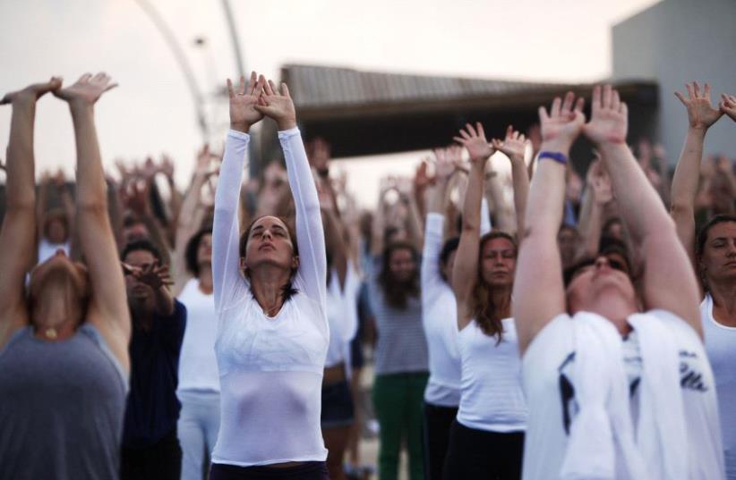 People practice yoga in Tel Aviv [File] (photo credit: REUTERS)