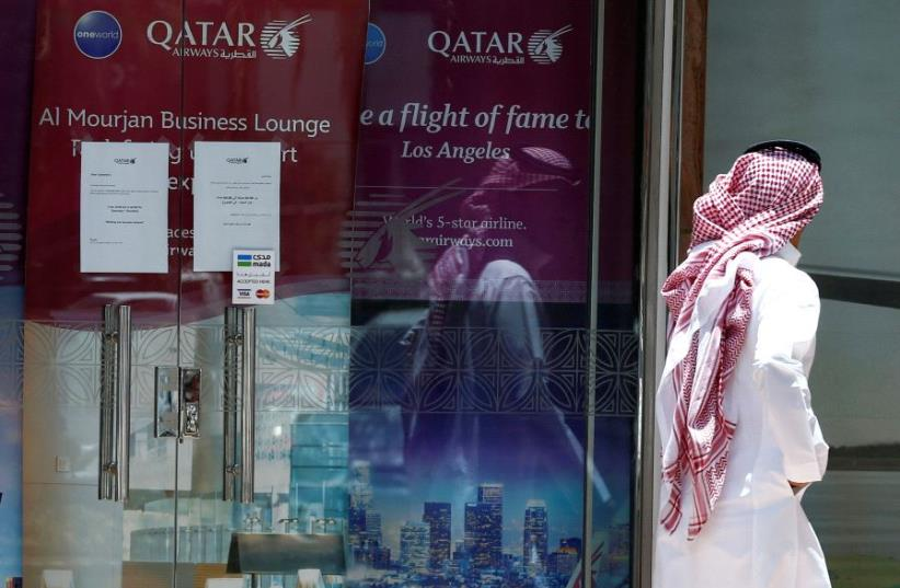 A man walks past Qatar Airways office in Riyadh, Saudi Arabia, June 5, 2017 (photo credit: REUTERS)