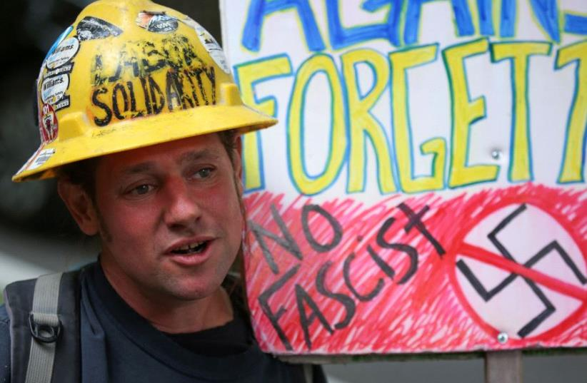 An protester holds an anti-Nazi and anti-fascist sign as conservative and anti-fascist groups hold concurrent rallies in Portland (photo credit: REUTERS)