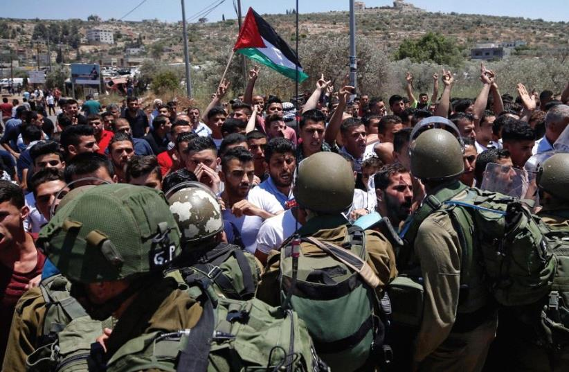 SOLDIERS TUSSLE with Palestinians in the West Bank village of Beita (photo credit: REUTERS)