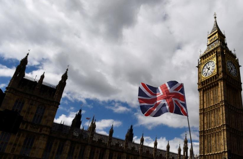 The Union Flag flies near the Houses of Parliament the day before a general election in central London, Britain June 7, 2017. (photo credit: REUTERS/CLODAGH KILCOYNE)