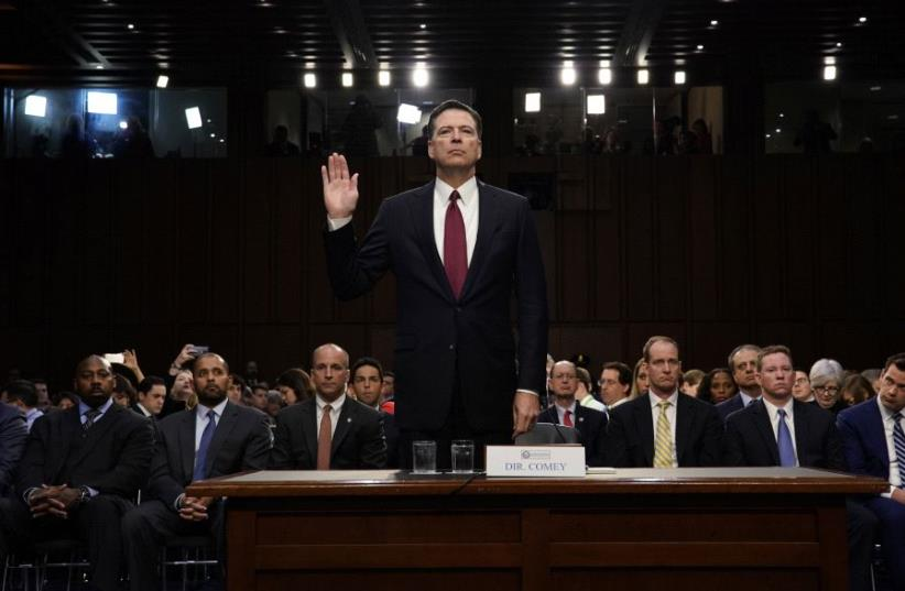 Former FBI Director James Comey is sworn in prior to testifying before a Senate Intelligence Committee hearing on Russia's alleged interference in the 2016 U.S. presidential election on Capitol Hill in Washington, US, June 8, 2017 (photo credit: REUTERS)