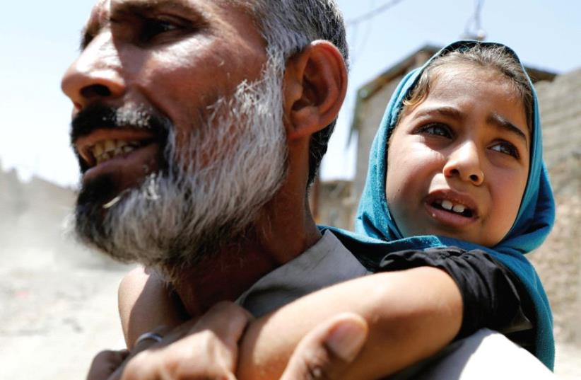 A MAN carries his daughter on his back after fleeing their home due to fighting between Iraqi forces and Islamic State fighters in Mosul's al-Zanjili district in Iraq (photo credit: REUTERS/ERIK DE CASTRO)