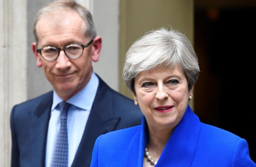 Britain's Prime Minister Theresa May leaves 10 Downing Street with her husband Philip to travel to Buckingham Palace to ask the Queen's permission to form a minority government, in London, June 9, 2017. (photo credit: REUTERS/TOBY MELVILLE)