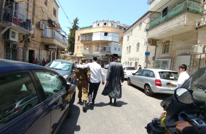 A TOLDOT AHARON Hassid (right) and another haredi man escort the son of former MK Dov Lipman, who is a soldier, away from an anti-Zionist mob in the capital's Mea She'arim neighborhood on Friday. (photo credit: HAREDI EXTREMISTS PROTESTS GROUP)