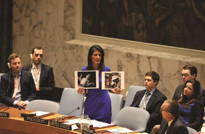 Nikki Haley montrant à l'ONU des photos  des victimes des armes chimiques d'Assad (photo credit: REUTERS)