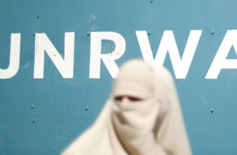 A veiled Muslim woman stands in front of a UNRWA sign (photo credit: REUTERS)