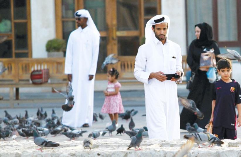 People look at pigeons at the Souq Waqif market in Doha, Qatar (photo credit: REUTERS)