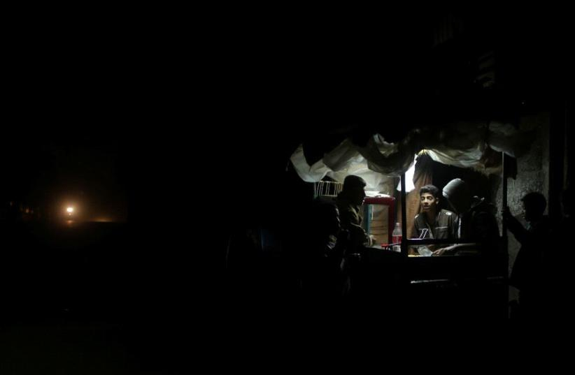 A Palestinian man sells falafel in a makeshift shop lit with a lamp powered by a battery during a power cut in Beit Lahiya in the northern Gaza Strip January 11, 2017. Picture taken January 11, 2017.  (photo credit: REUTERS/MOHAMMED SALEM)