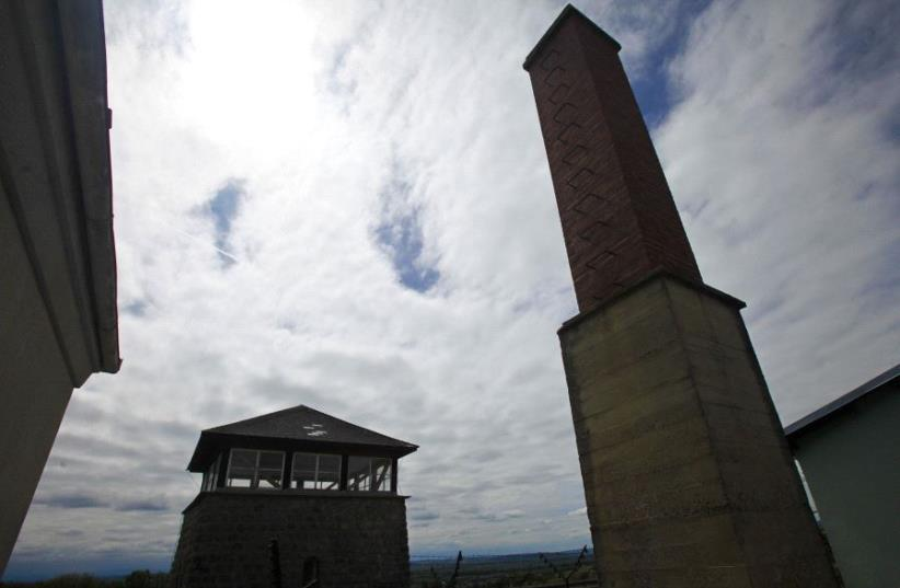 A view of the watch tower and a chimney of the former Austrian Nazi concentration camp in Mauthausen May 7, 2010.  (photo credit: REUTERS/HERWIG PRAMMER)